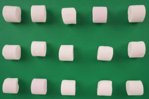 Pattern with marshmallow candies on green stock image