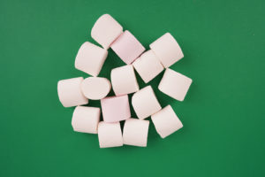 White marshmallow on green background stock photo