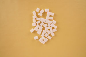 Sugar cubes on carrot background stock photo